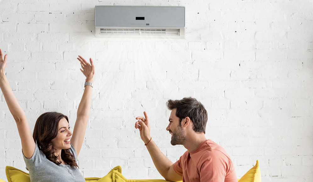 Couple sitting in front of a AC