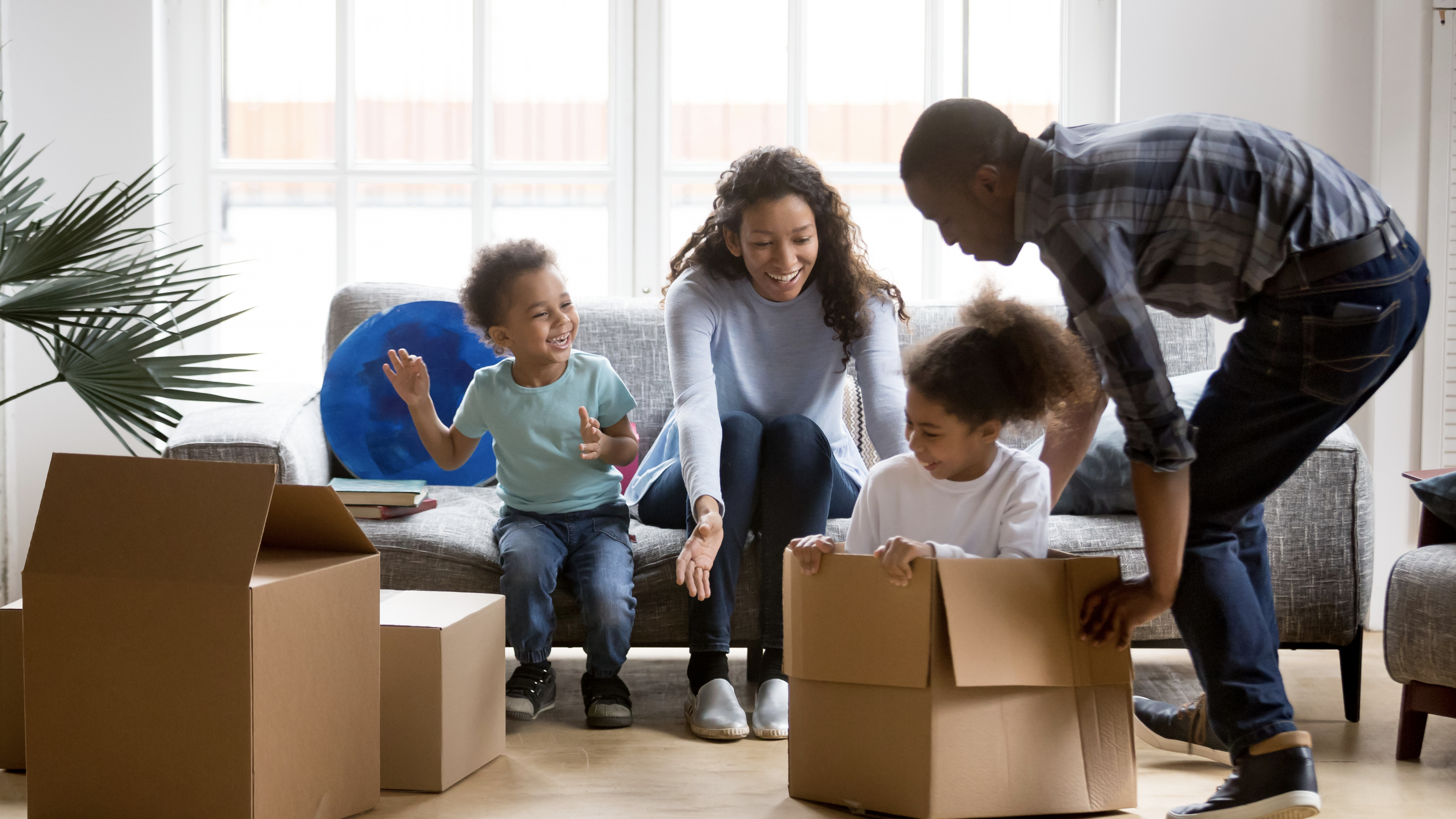 Happy playful African American family moving in new apartment