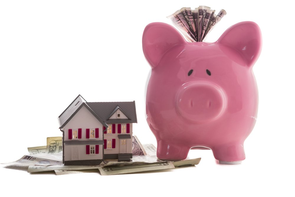 Close up of a pink piggy bank with dollars beside miniature house model on white background