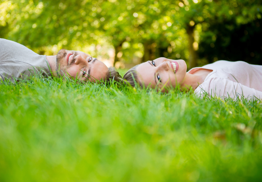 Young loving couple lying at the park  with heads together